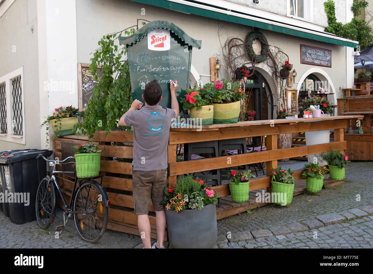 Un camarero en el restaurante Zirkelwirt puestos en Salzburgo, Austria el menú diario ofertas en una pizarra fuera del restaurante. Foto de stock