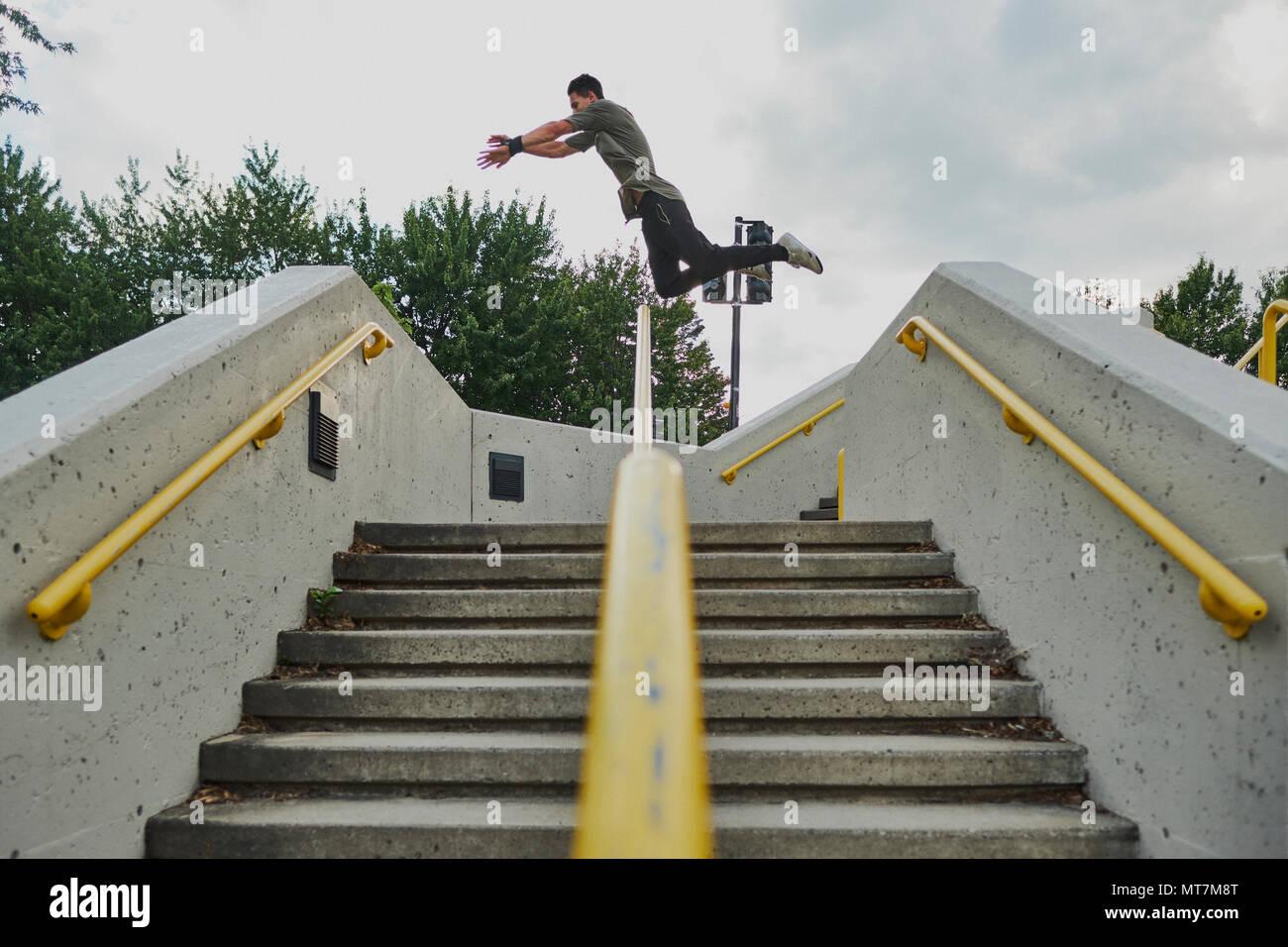 Adolescente saltando sobre una estructura de hormigón, mientras haciendo parkour Imagen De Stock