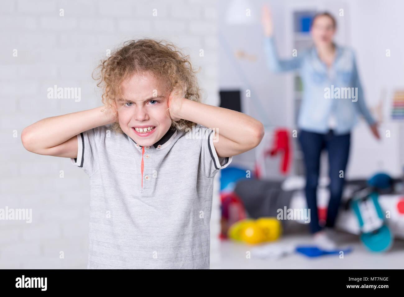 Hijo rebelde cubriendo sus orejas, madre gritando en segundo plano. Foto de stock