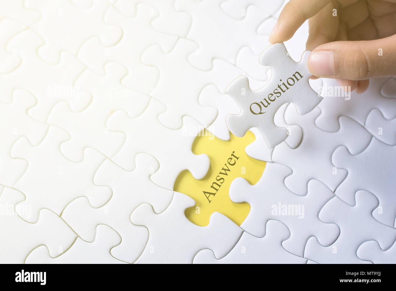 Mano sujetando question and answer word en rompecabezas. q&a, preguntas frecuentes y pregunta concepto Imagen De Stock