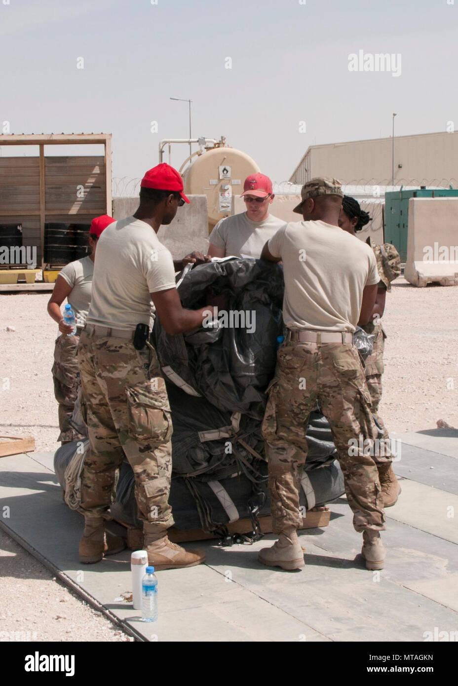 Los soldados de la 824ª Compañía de intendencia paracaídas pila utilizado para la entrega aérea en la base aérea de Al Udeid, Qatar, el 19 de abril de 2017. Operaciones de entrega aérea son esenciales para llevar suministros a las tropas en el Oriente Medio cuando los medios convencionales de transporte no son factibles. Foto de stock