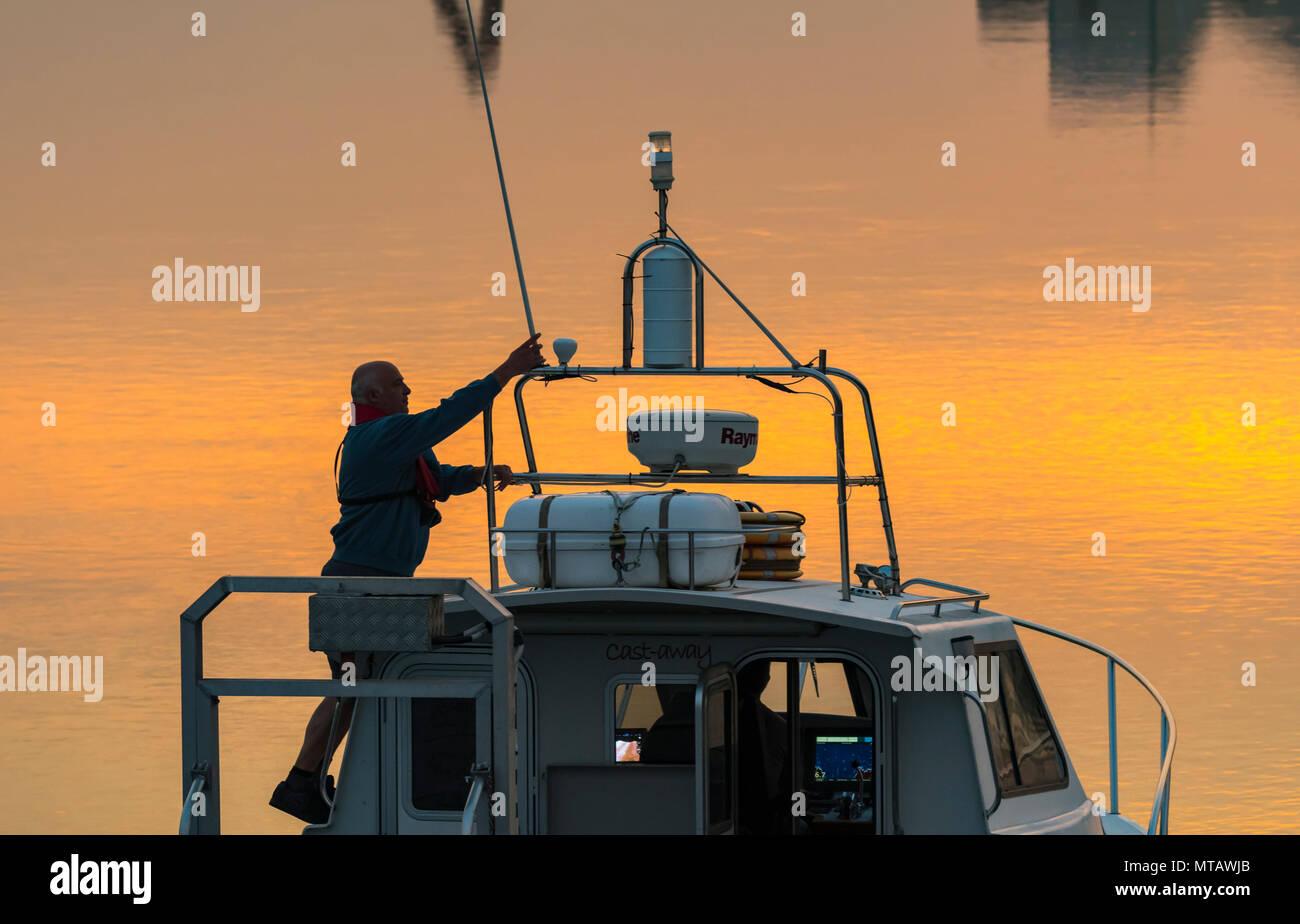 Barco en un río al anochecer, regresando a casa después de un viaje en el mar, con la luz del atardecer y reflejos naranjas del cielo de la tarde en el agua. Going Home concepto. Imagen De Stock