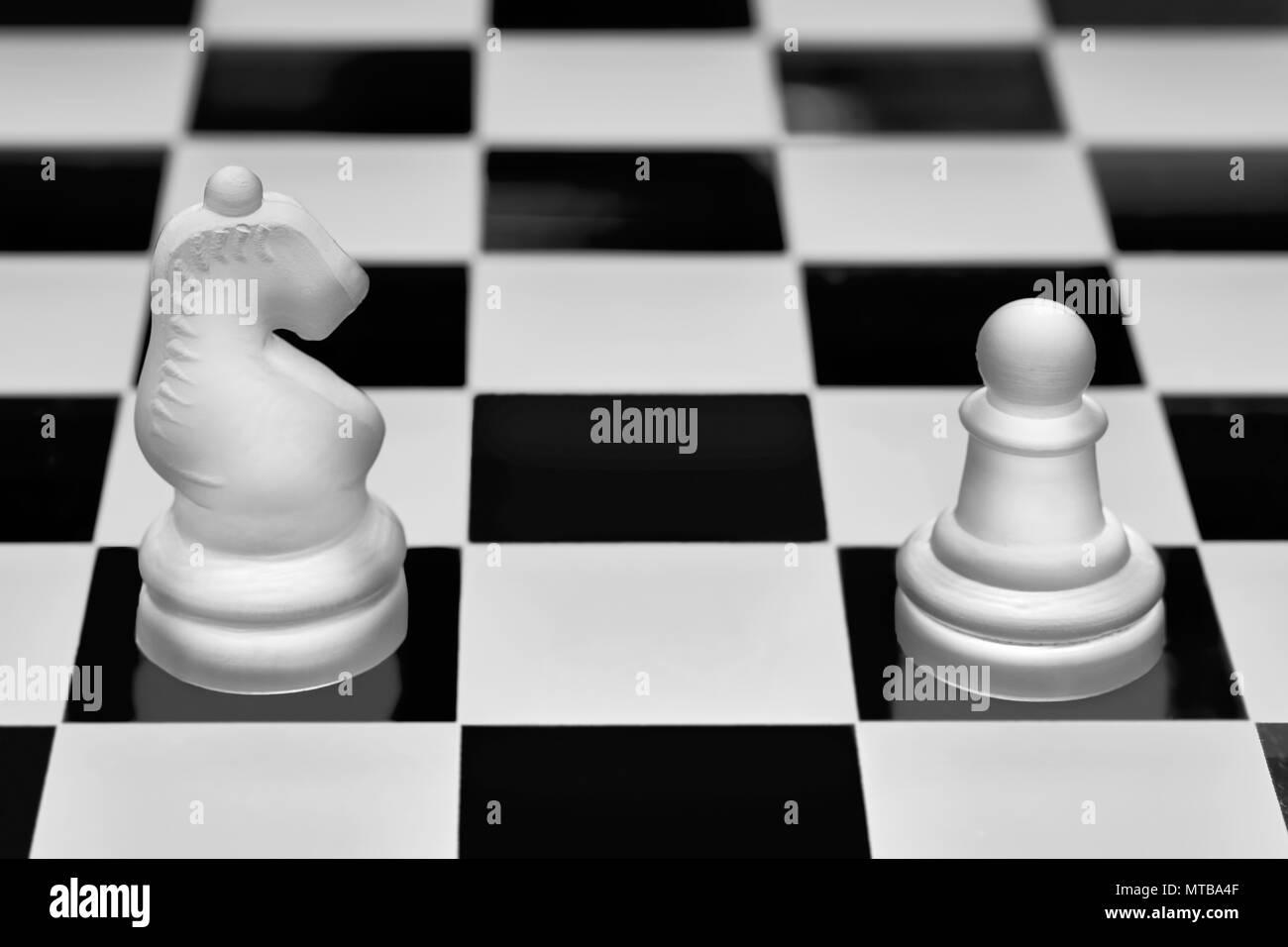 Las piezas de juego de ajedrez. El caballero y peón de uno contra el otro. Concepto de oposición y confrontación. Imagen De Stock