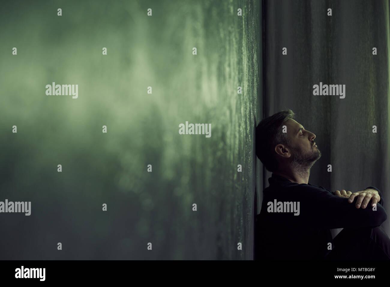 Pisado el hombre sentado solo en la habitación sombría Imagen De Stock