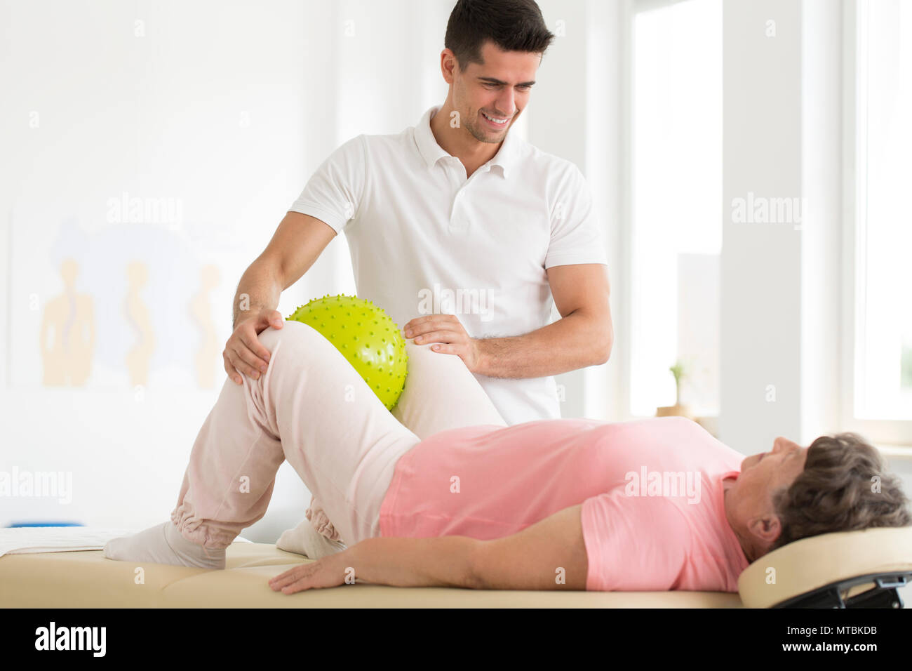 Paciente apretar una bola de masaje verde con las rodillas mientras está acostada sobre su espalda Imagen De Stock
