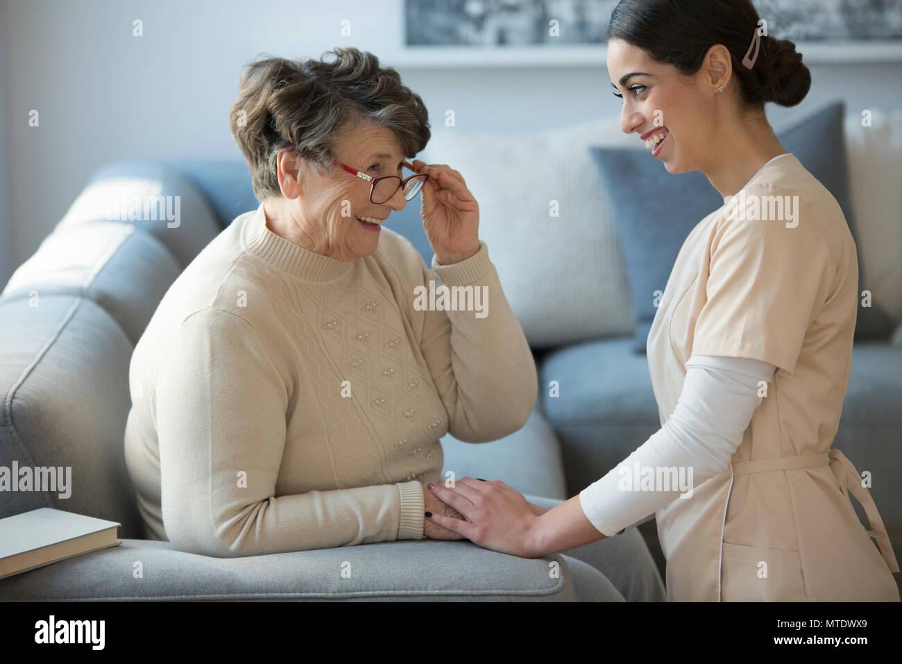 Un cuidador de licitación de rodillas y frente a una anciana sonriente que está sentado en un sofá y manteniendo sus gafas Imagen De Stock