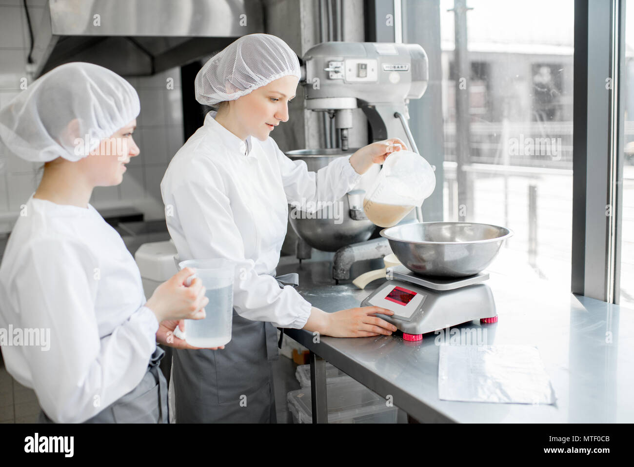 Dos mujeres en uniforme confiteros pesando los ingredientes para pastelería trabajan en la fabricación de panadería Foto de stock