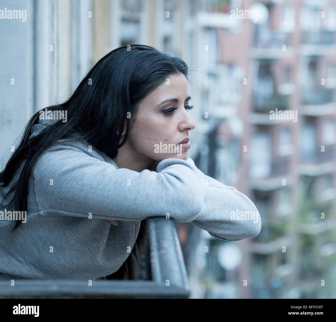 Hermosa latina pisado solitaria mujer mirando por sentimientos de tristeza, dolor y preocupación en un balcón de la casa. Crisis, depresión y salud mental concepto Imagen De Stock