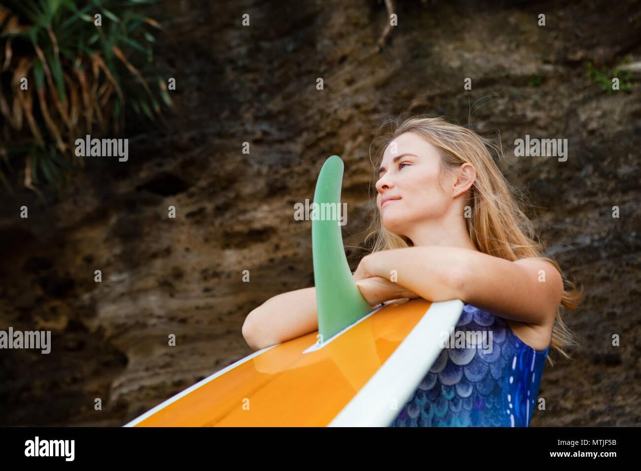 Chica en Bikini deportivo con soporte de tabla de surf por el acantilado negro en la playa. Surfer mujer mira al mar y surfear olas. Las personas activas en el deporte aventura Imagen De Stock