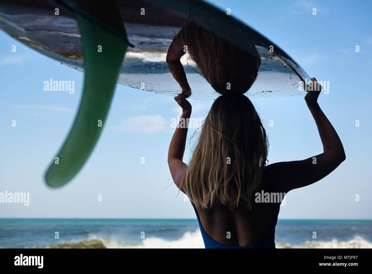 Chica en Bikini con tablas de surf a pie de playa de arena negra. Surfer mujer mira al mar y piscina de agua surf con espuma blanca. Las personas activas en el deporte aventura Imagen De Stock