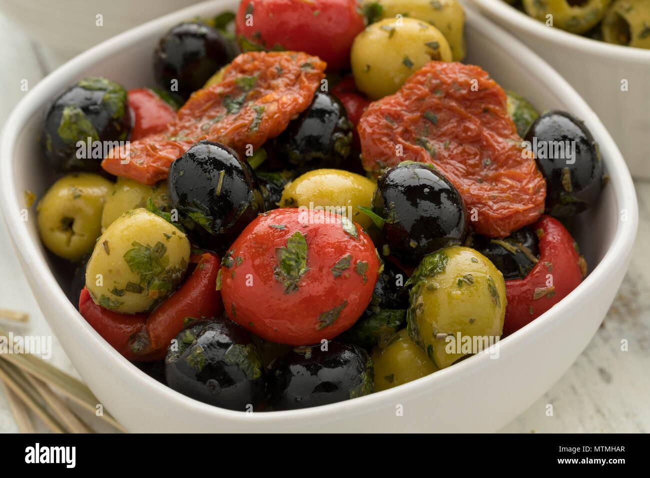 Recipiente con verde y negro, aceitunas, pimientos y tomates como snack cerrar Foto de stock