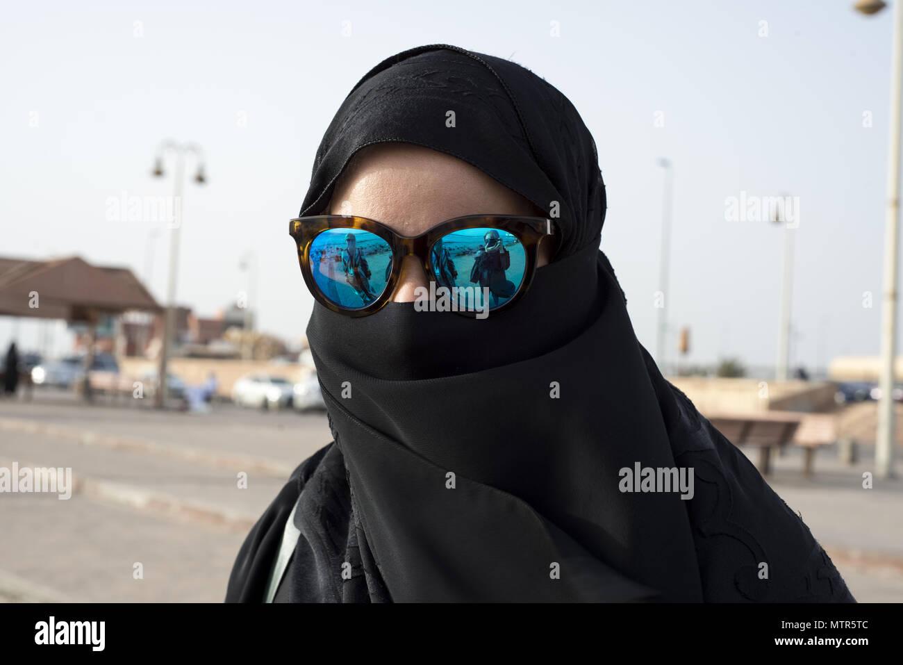 La mujer saudita vistiendo una abaya negra y hiyab protege sus ojos del sol con gafas de sol azul Imagen De Stock