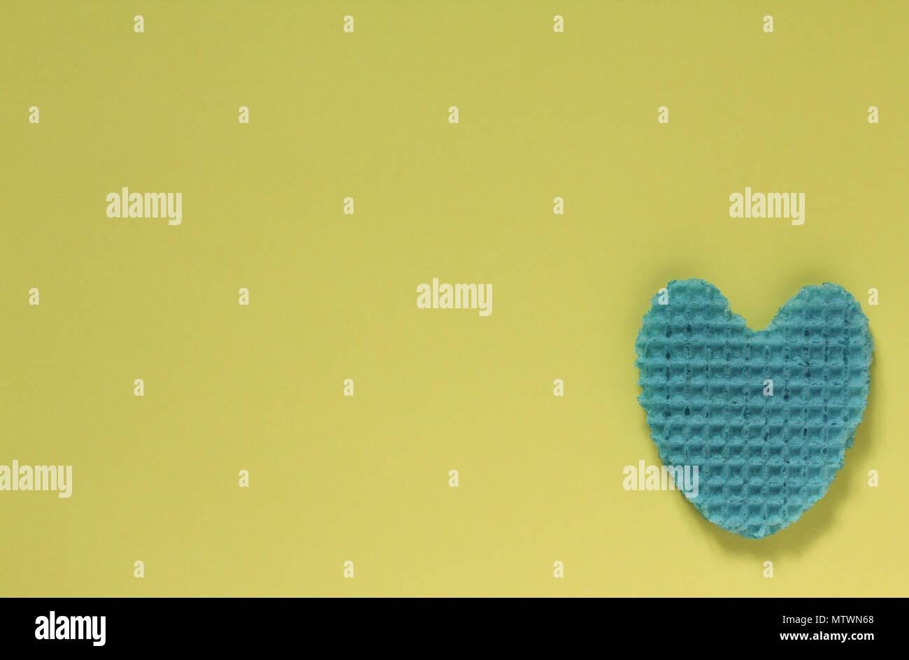 Corazón creativo de una oblea comestible azul en color pastel. La ...
