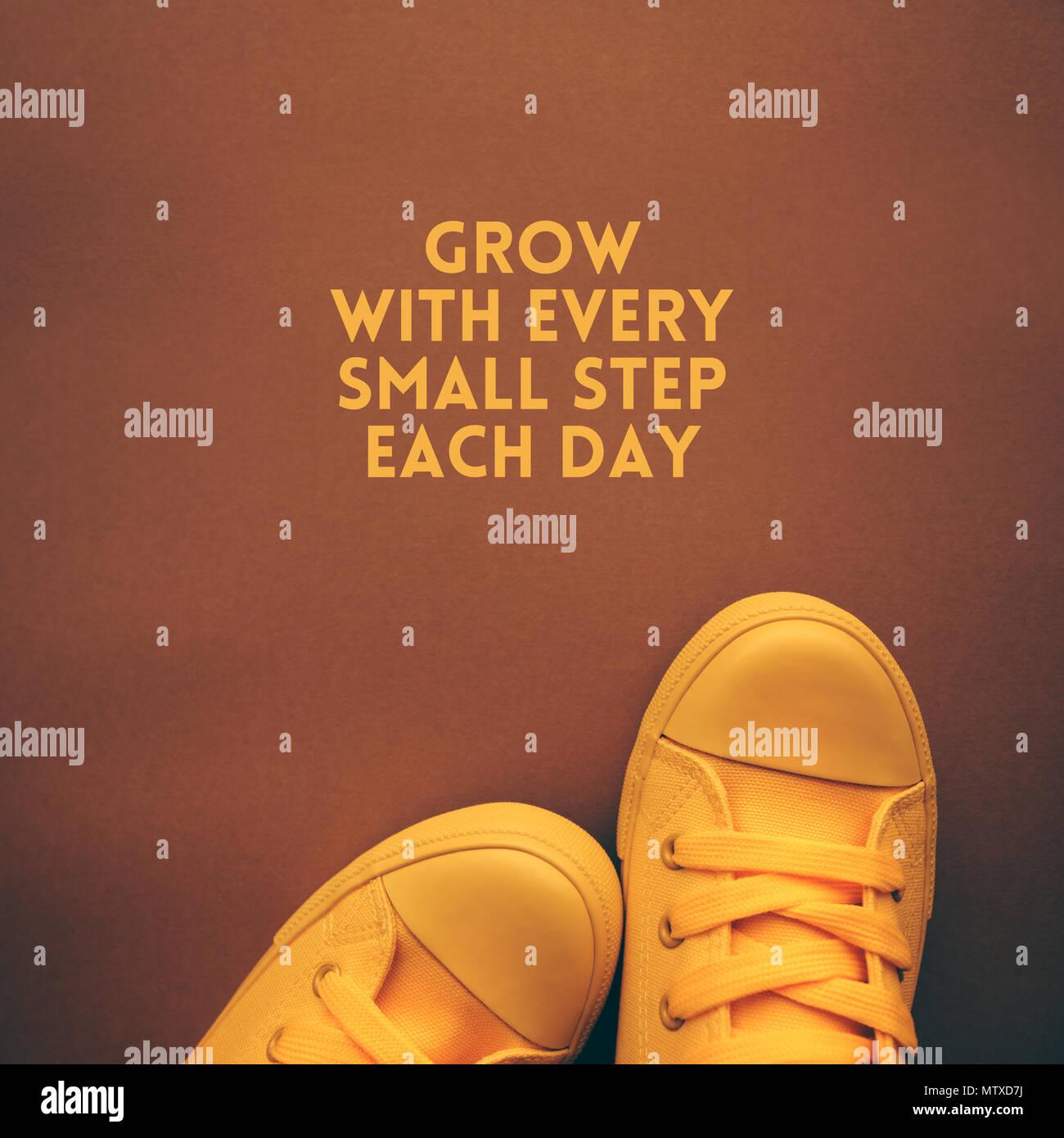 Crecen con cada pequeño paso cada día cita con la motivación del joven en amarillo zapatillas de pie encima del texto Imagen De Stock