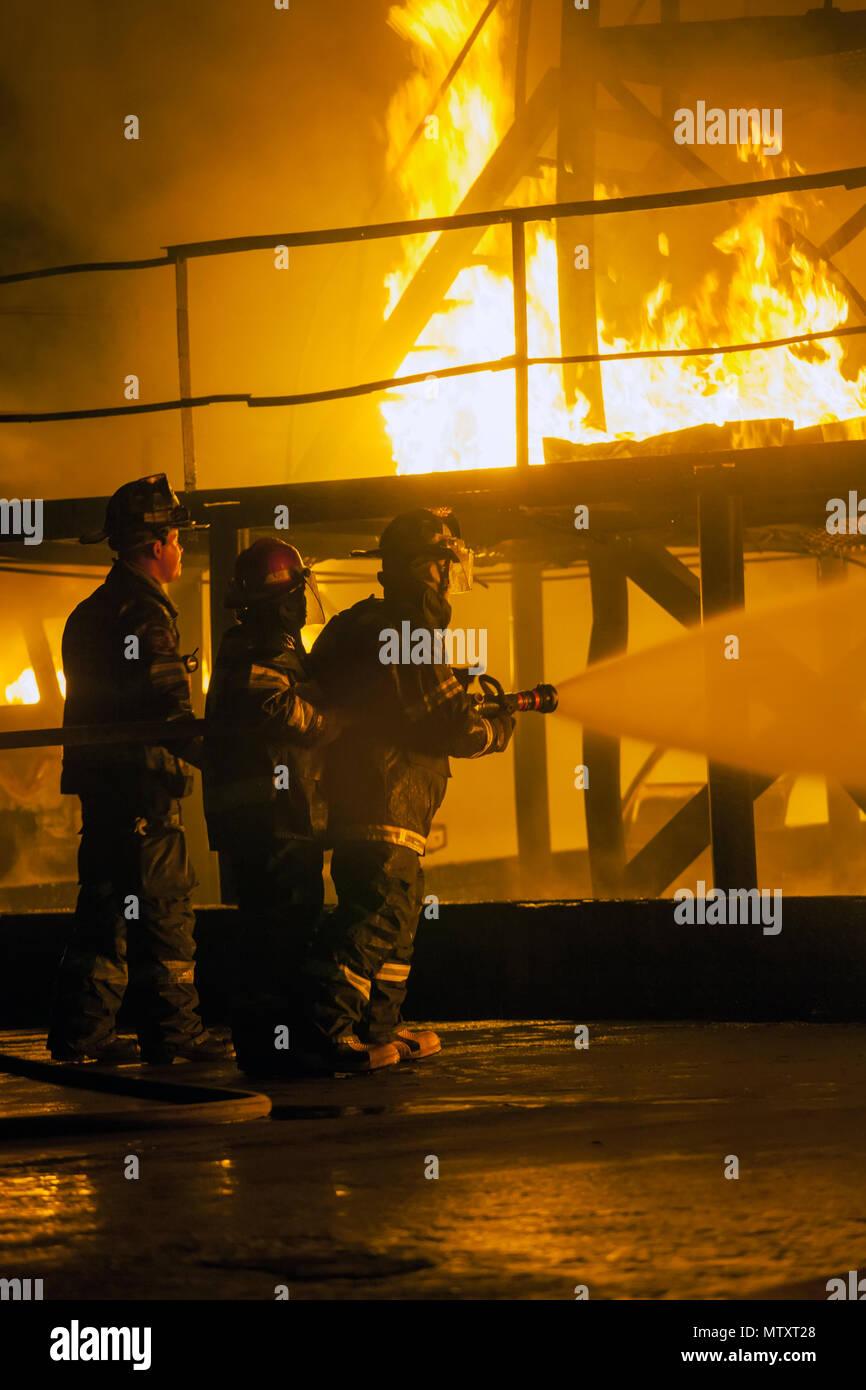 Johannesburgo, Sudáfrica: Mayo, 2018 Bomberos rociado de agua en la estructura de la quema durante ejercicios de entrenamiento de extinción de incendios Imagen De Stock