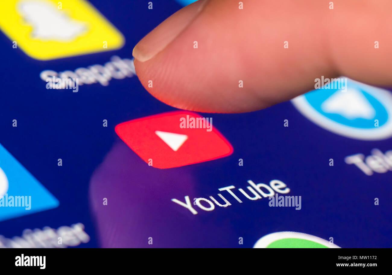 Dedo pulsando el icono de Youtube para cargar la aplicación en un smartphone o la tableta táctil. Imagen De Stock