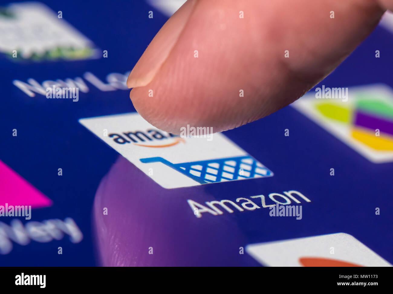 Dedo pulsando el icono de Amazon para cargar la aplicación en un smartphone o la tableta táctil. Imagen De Stock