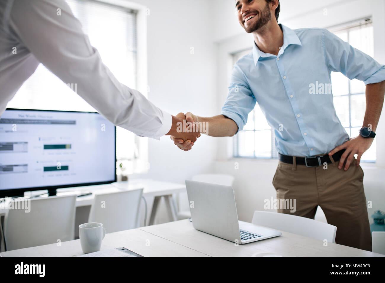 Los compañeros de negocio un apretón de manos en la mesa de conferencias. Empresario feliz saludo colega en la sala de reunión. Imagen De Stock