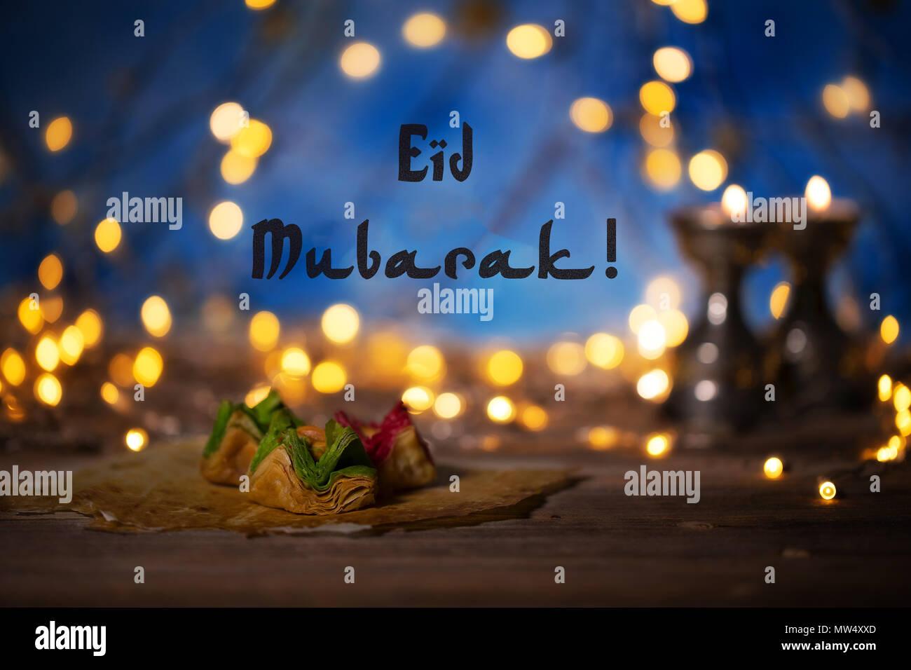 Felicitación: Eid Mubarak! Dulces árabes sobre una superficie de madera. Portavelas, luz de noche y noche azul cielo con luna creciente en el fondo. Foto de stock