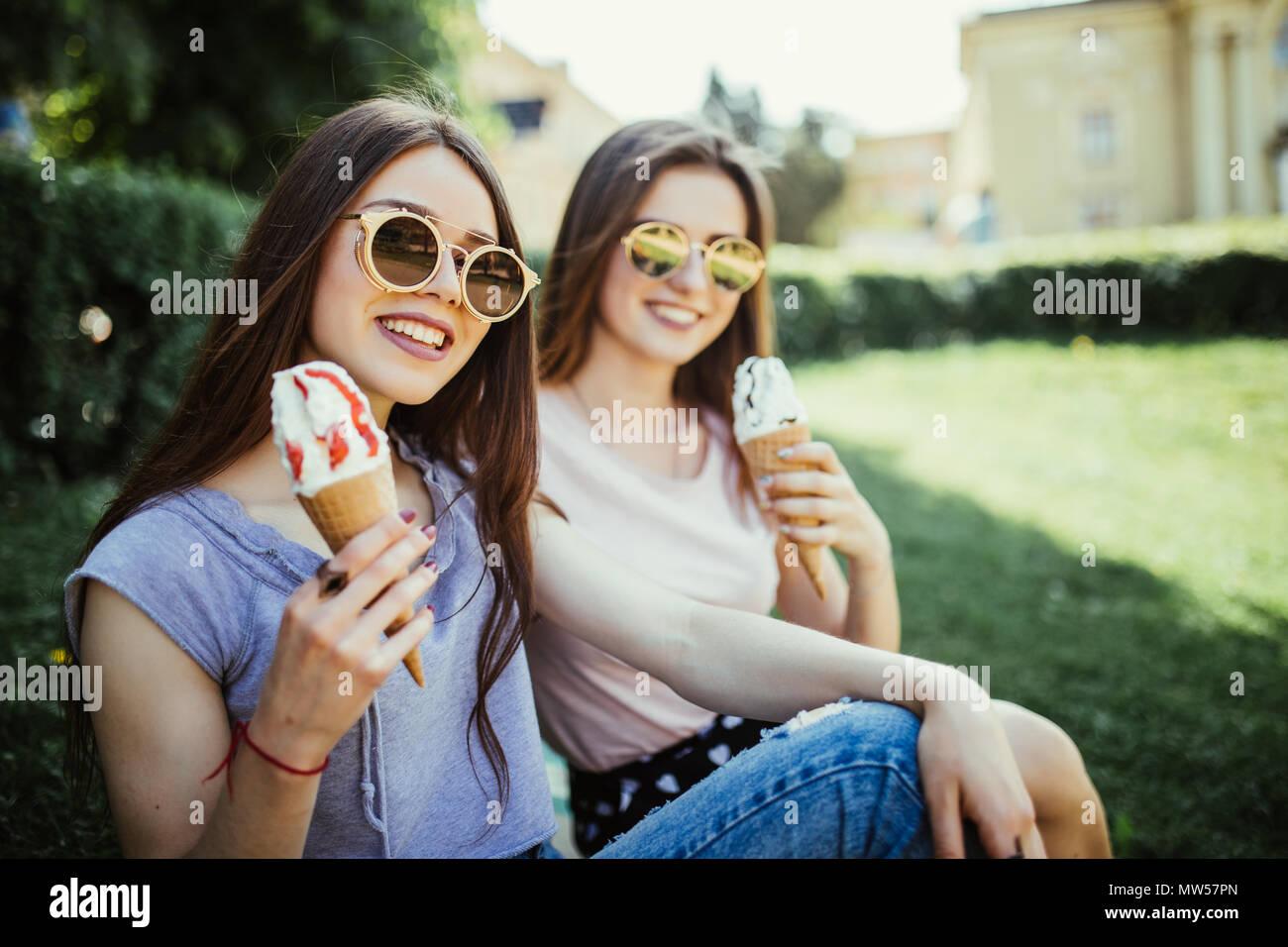 Dos mujeres jóvenes amigos comer helado sentado en la hierba en las calles de la ciudad Imagen De Stock