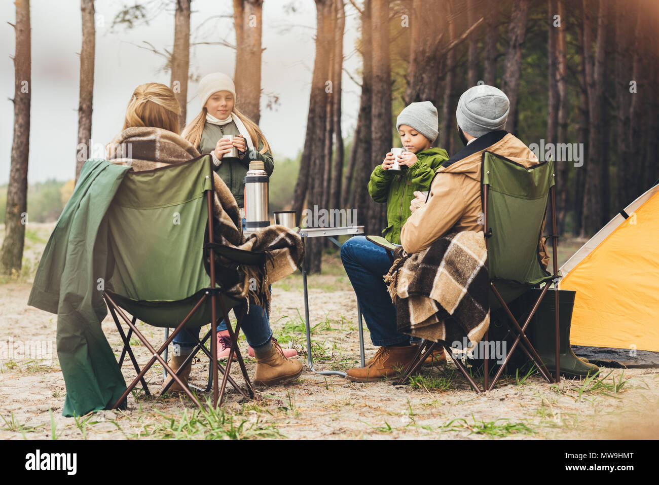 Hermosa familia beber té caliente mientras habiendo camping Imagen De Stock
