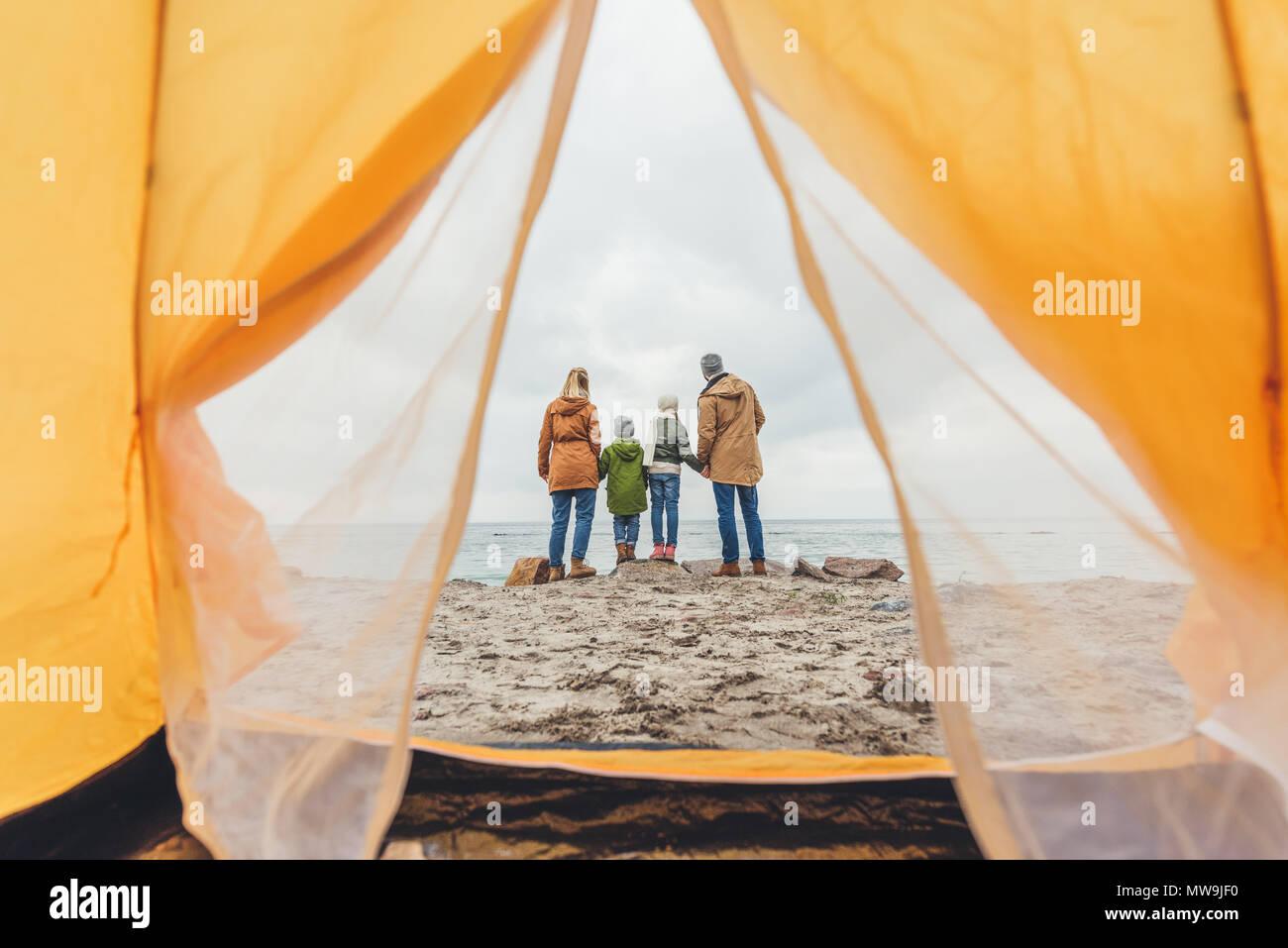 Familia de pie junto a la orilla y mirando el mar Imagen De Stock