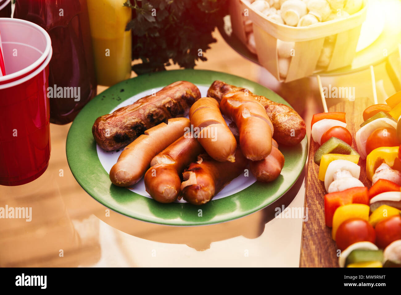 Salchichas cocidas en la parrilla al aire libre servido en la placa Foto de stock