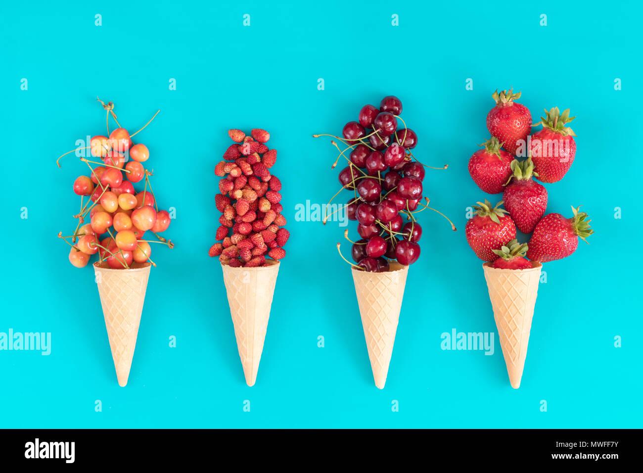 Cuatro conos waffle con cerezas rojas, fresas, cerezas amarillas y strawberryes sobre azul de la superficie. Sentar planas, vista superior alimentos dulces de fondo. Imagen De Stock