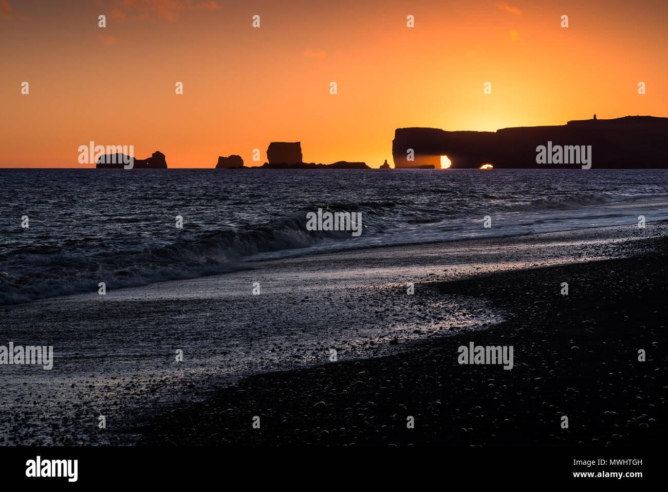 Con una preciosa vista al faro de Dyrholaey y rocas. Imagen De Stock