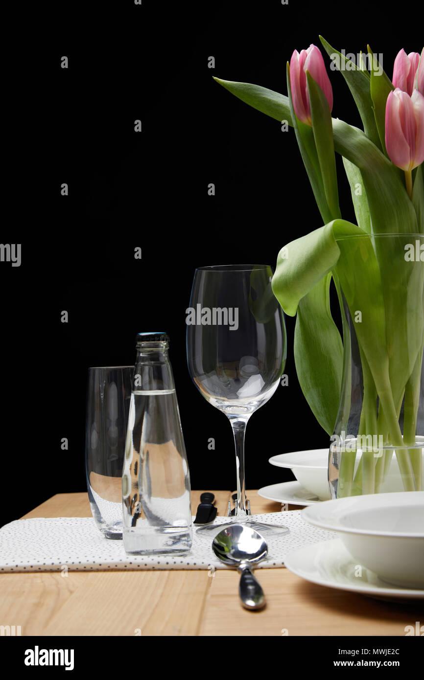 Jarrón con ramo de flores en la mesa con vajilla festiva Foto de stock