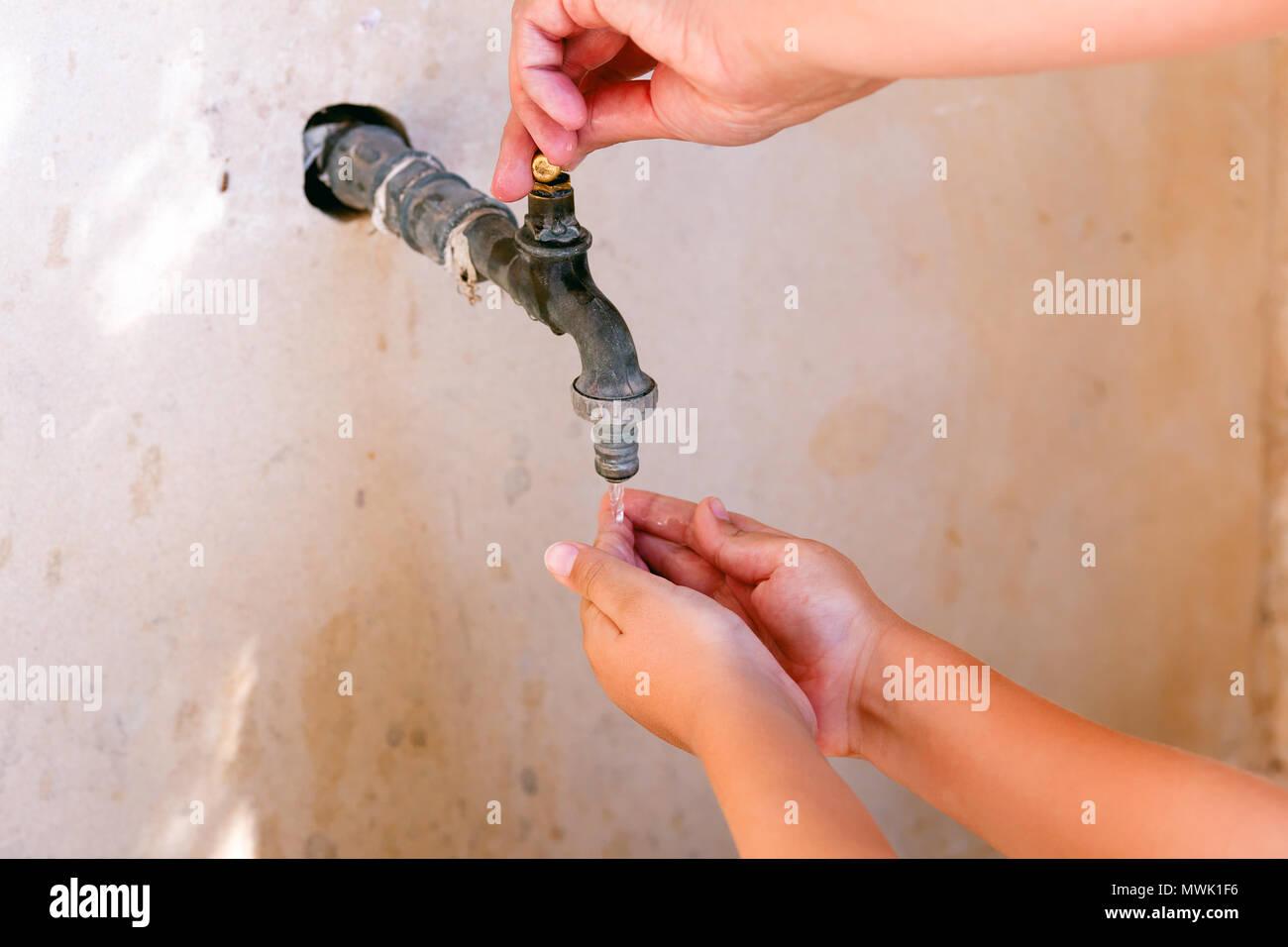 Grifo de agua abierto mano de mujer y niño lavándose las manos. Close-up. Imagen De Stock