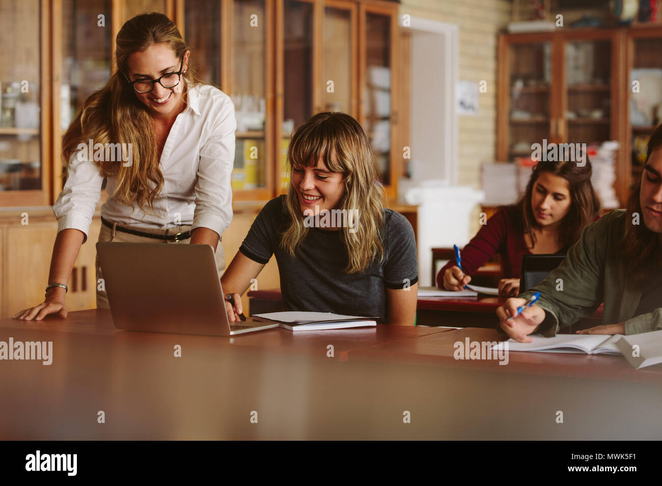 Profesor feliz ayudando a su estudiante en la escuela secundaria. Mujer con portátil con su maestro de pie y sonriente en el aula. Foto de stock