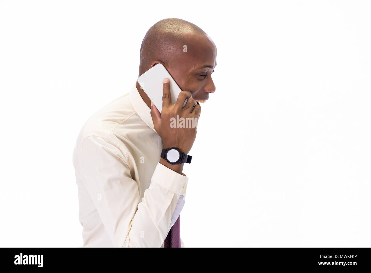 Entusiasmada y feliz hombre afroamericano vistiendo una camisa y corbata hablando por el teléfono, abrumadora con buenas noticias y felicidad Foto de stock