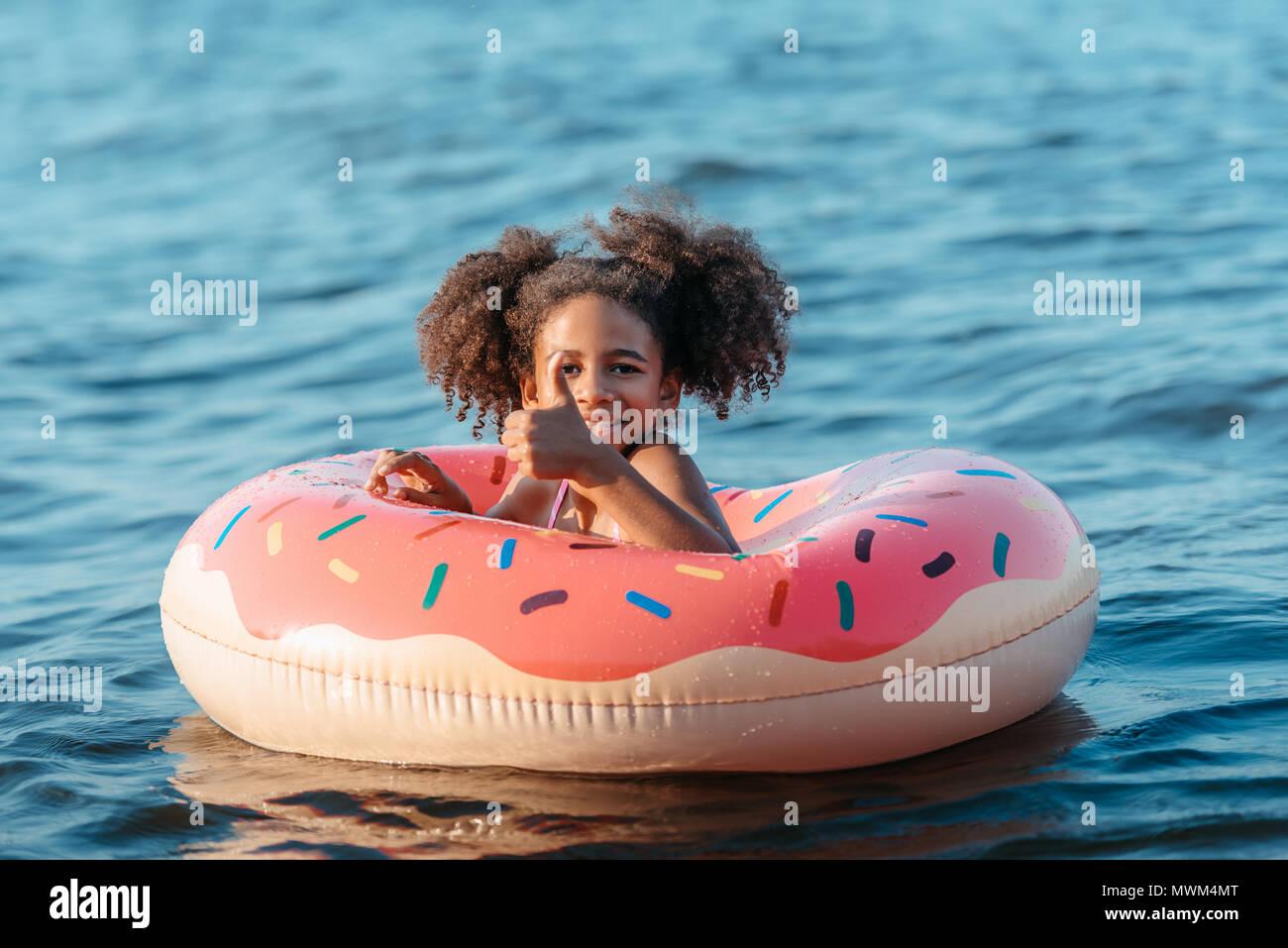 Cute sonriente joven afroamericano nadando en anillo de caucho y mostrando el pulgar hacia arriba Imagen De Stock