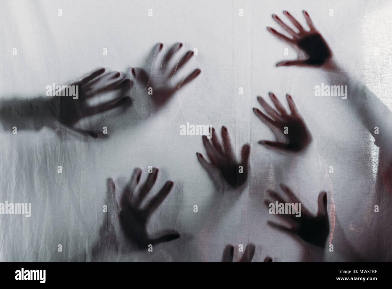 Miedo borrosas siluetas de manos humanas tocar el vidrio esmerilado Imagen De Stock