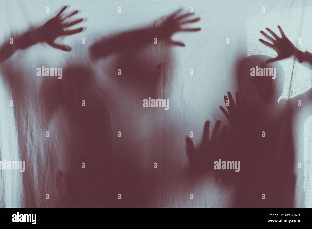 Miedo borrosas siluetas de personas tocando el vidrio esmerilado con manos Imagen De Stock
