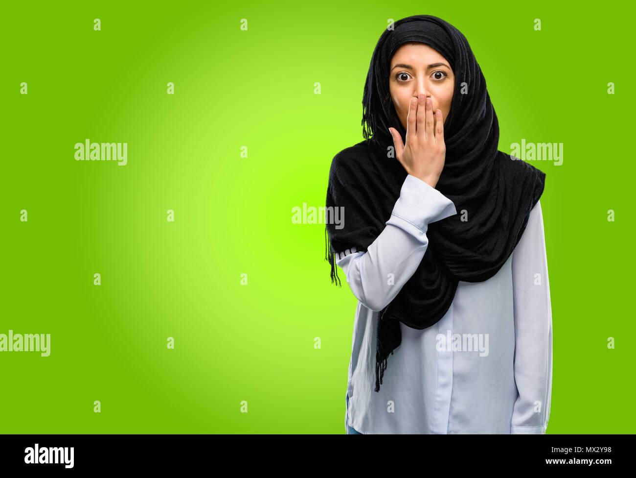 Joven árabe mujer vistiendo el hijab cubre boca en estado de shock, parece tímido, expresando el silencio y confundir los conceptos, asustada Foto de stock