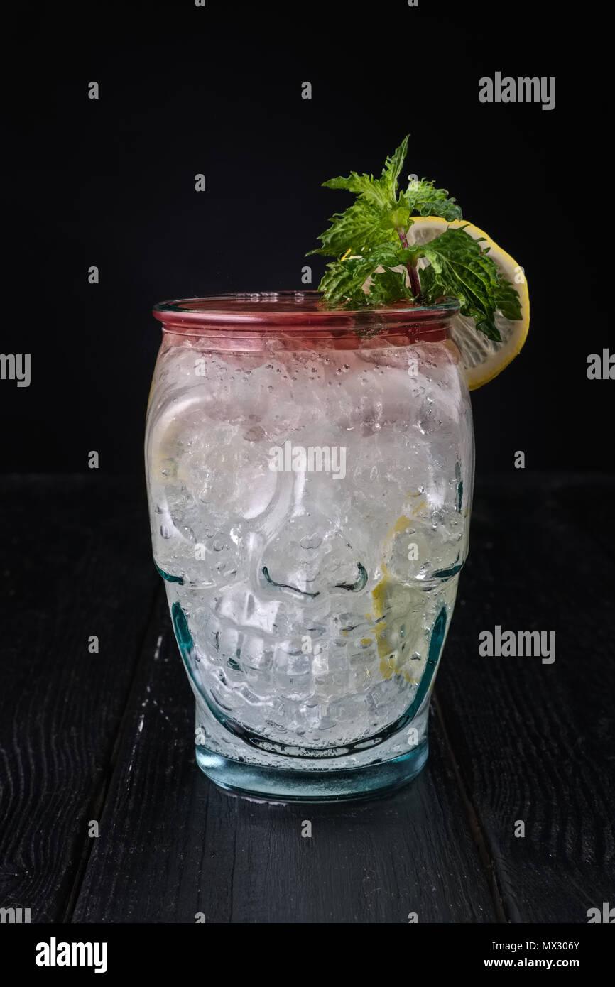 Variación de gin tonic cóctel con jarabe de cereza en la copa de cráneo Foto de stock
