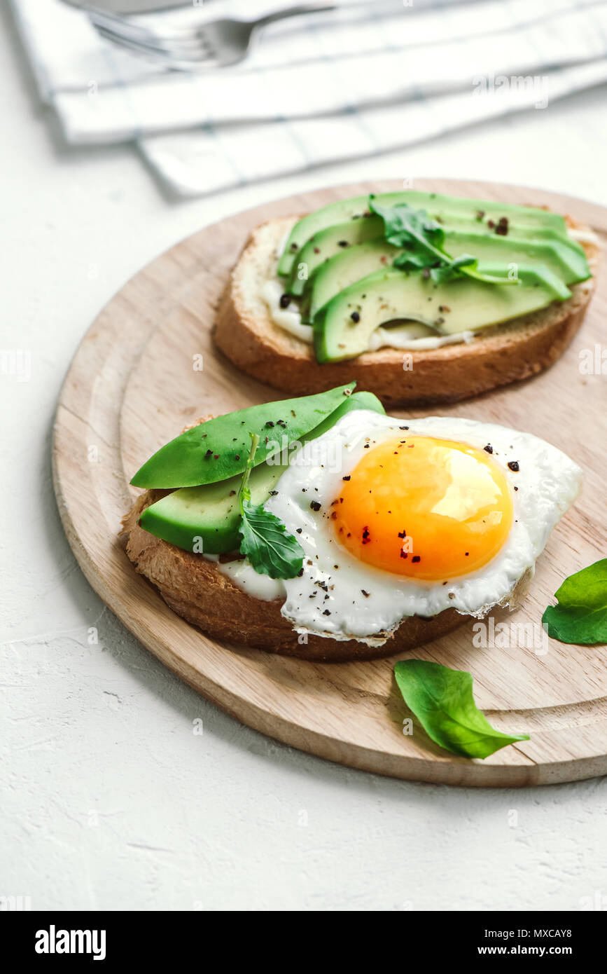 Sándwich de aguacate con huevo frito - rodajas de aguacate y huevo sobre pan tostado para el desayuno o la merienda, copie el espacio. Imagen De Stock