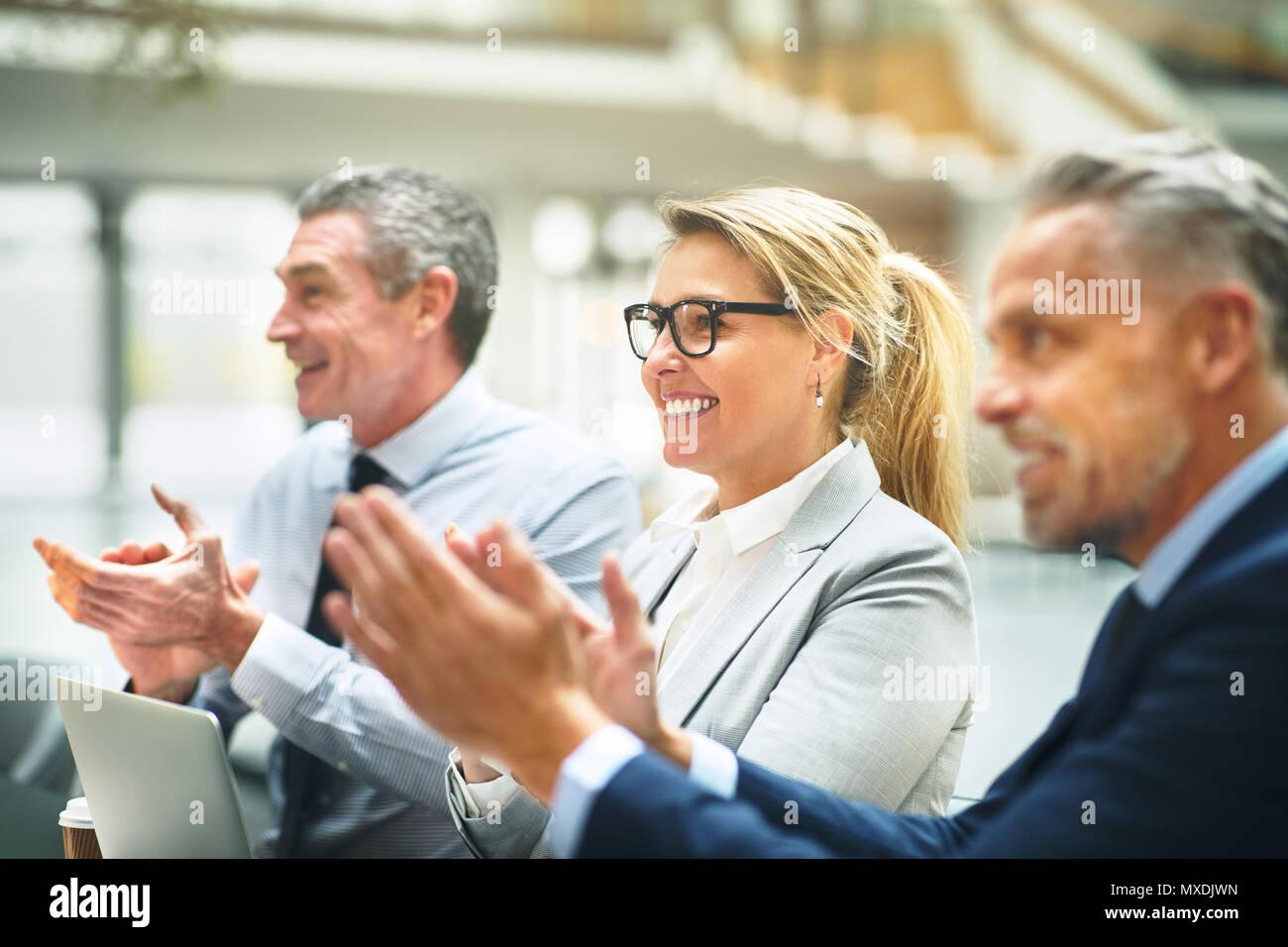 Grupo maduro de empresarios sentados juntos en una mesa en una moderna oficina sonriendo y aplaudiendo después de una presentación Foto de stock