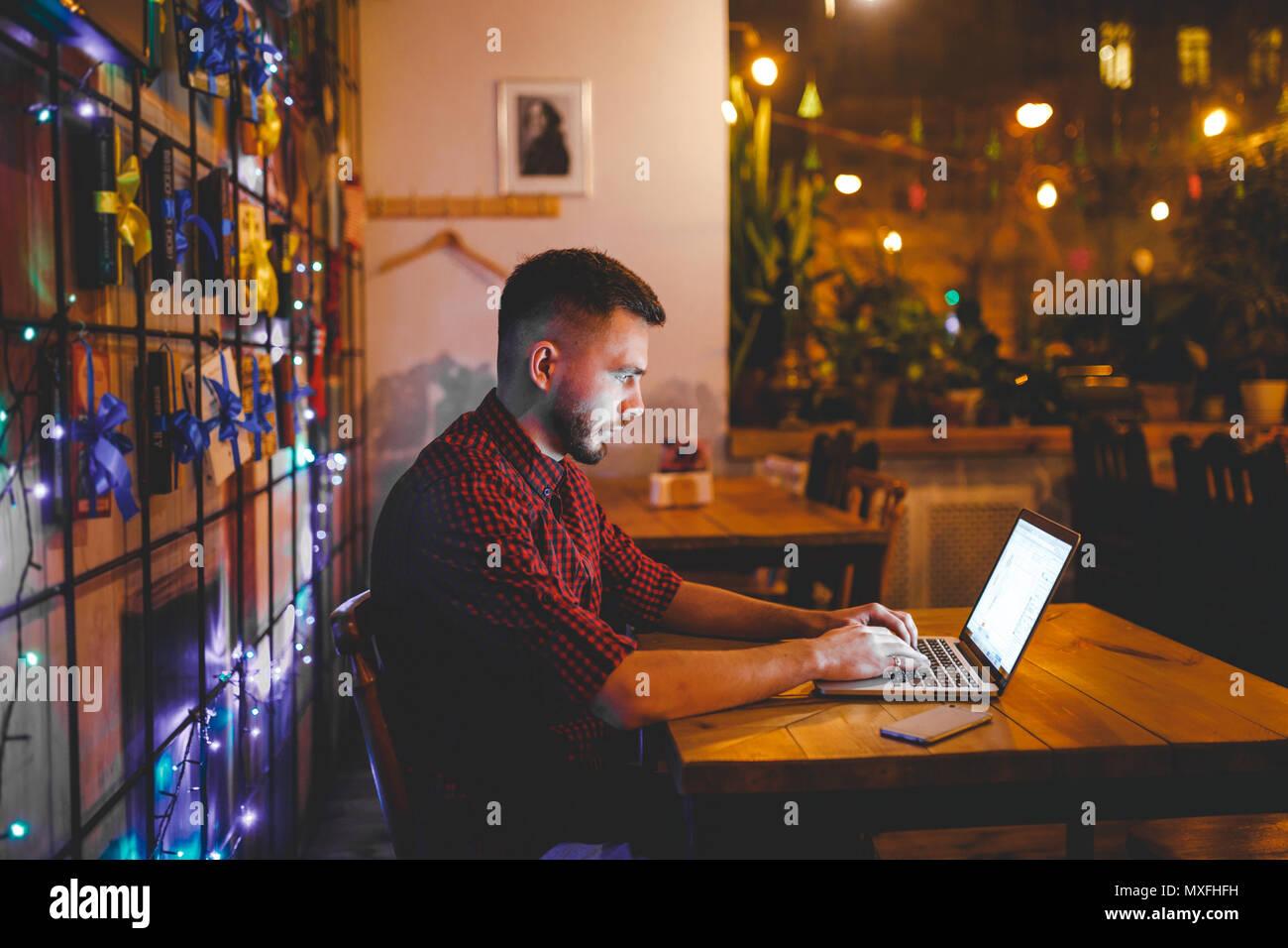 Un joven apuesto hombre caucásico con barba y gran sonrisa en una camisa a cuadros roja está trabajando detrás de un portátil gris sentado en una mesa de madera. Las manos sobre el teclado. En la tarde en la cafetería Imagen De Stock