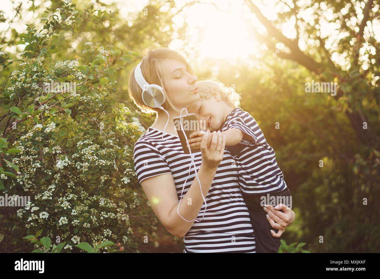 Madre e hijo en rayas T-shirts. Mujer escucha música con los auriculares y el muchacho sostiene en sus brazos. Él está sosteniendo el teléfono celular y hacer selfie. Familia Imagen De Stock