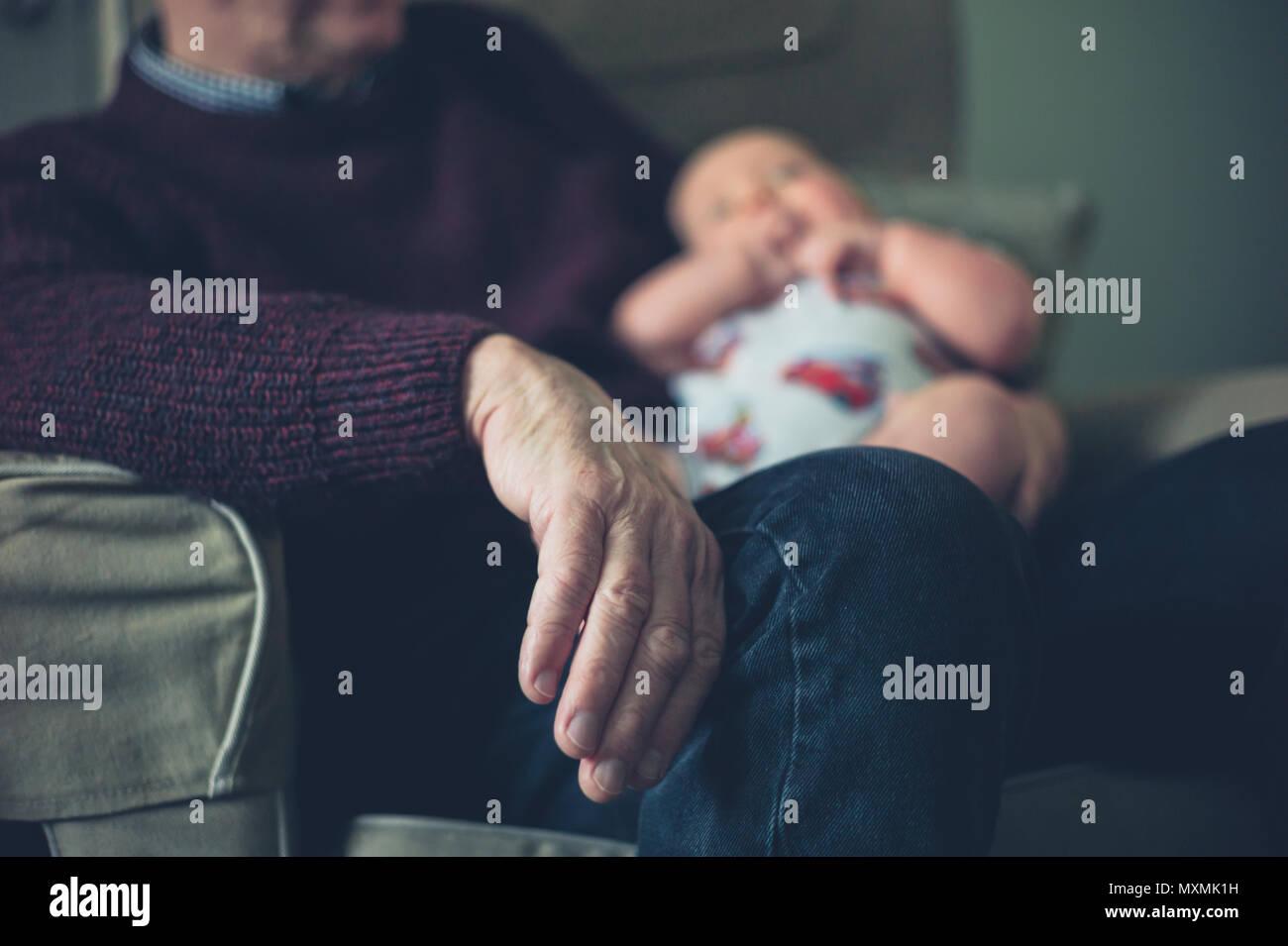 Un abuelo está sentado en una silla en su casa con su nieto Imagen De Stock
