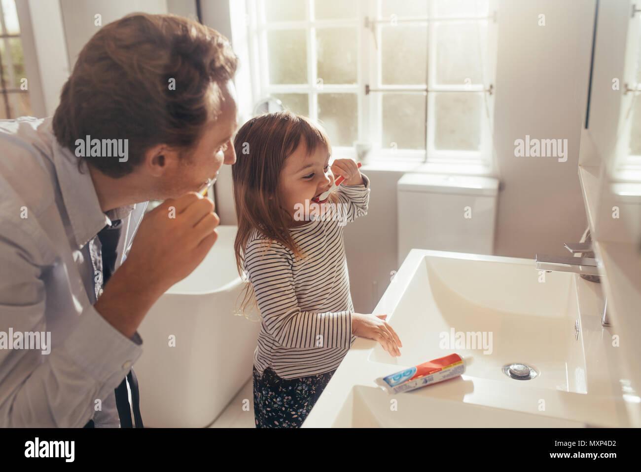 Padre e hija cepillarse los dientes de pie en el baño. El hombre enseñar a su hija cómo cepillarse los dientes. Imagen De Stock