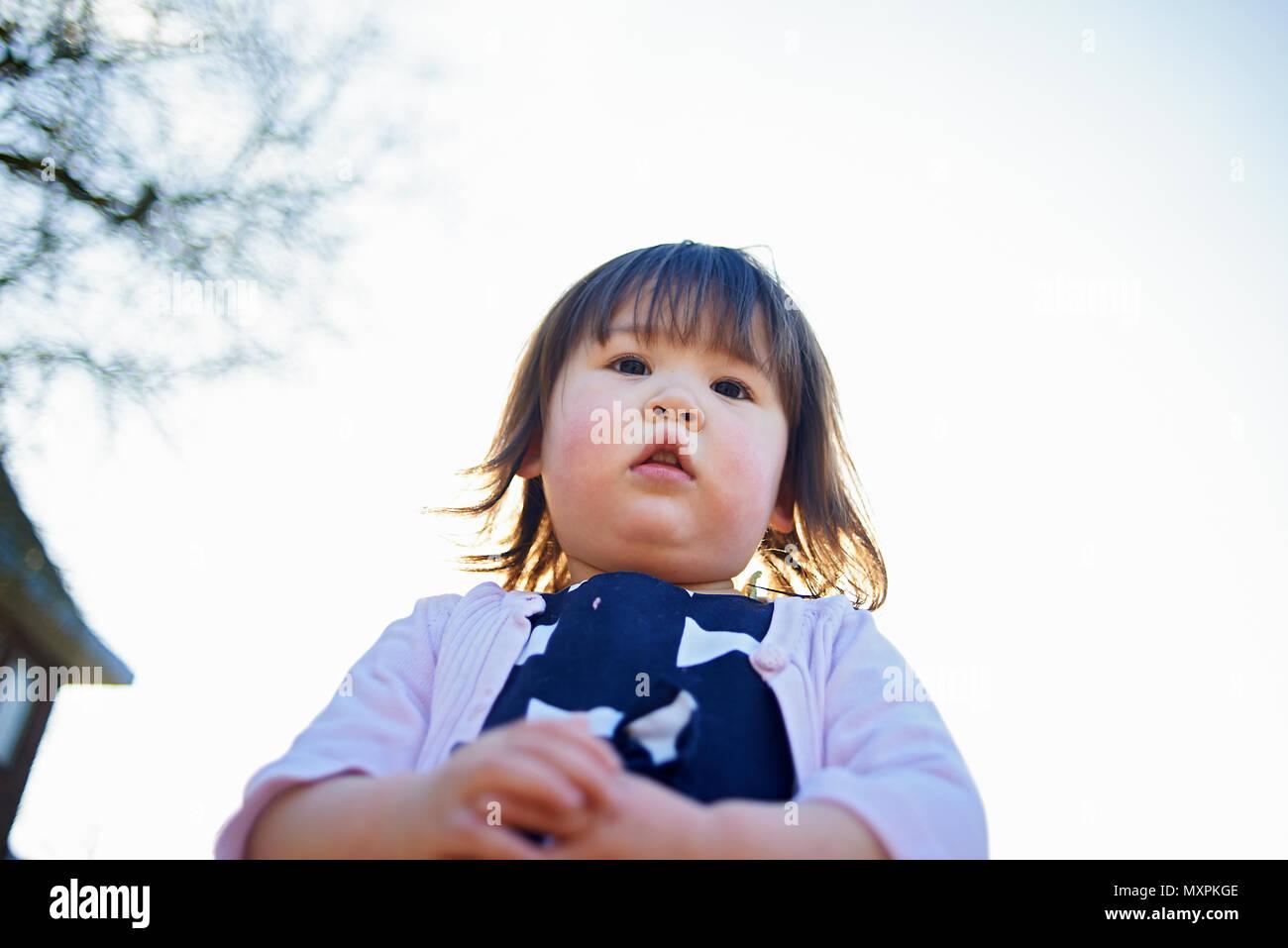 Retrato de un joven asiático lindo bebé niña con rosey mejillas en clima  frío mirando a 253d8059a14