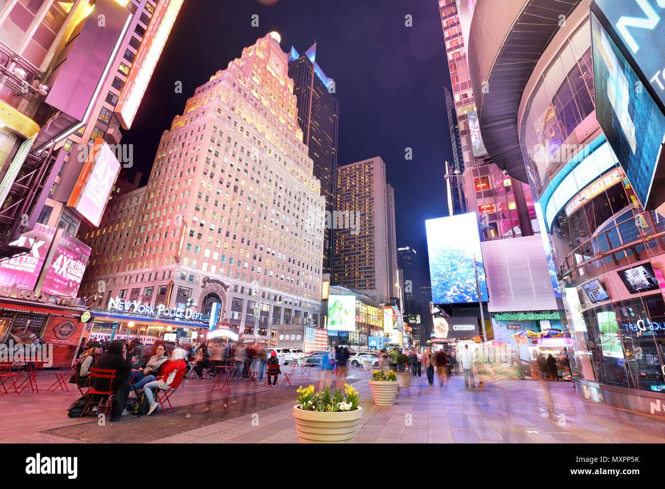 Nueva York, Estados Unidos - 12 de abril: La arquitectura de la famosa Times Square en la ciudad de Nueva York, EE.UU., con sus luces de neón y paneles en la noche y un montón de tour Imagen De Stock