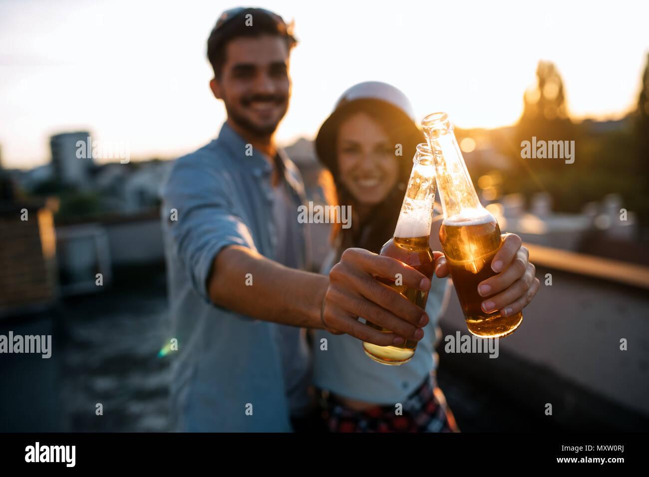 Joven feliz pareja brindando con cerveza al aire libre Foto de stock