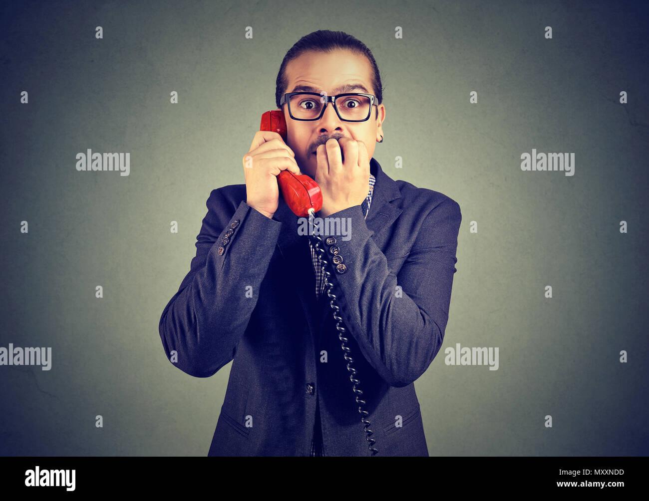 Hombre elegante en traje recibir noticias alarmantes sobre el teléfono y mirando a la cámara con miedo. Foto de stock