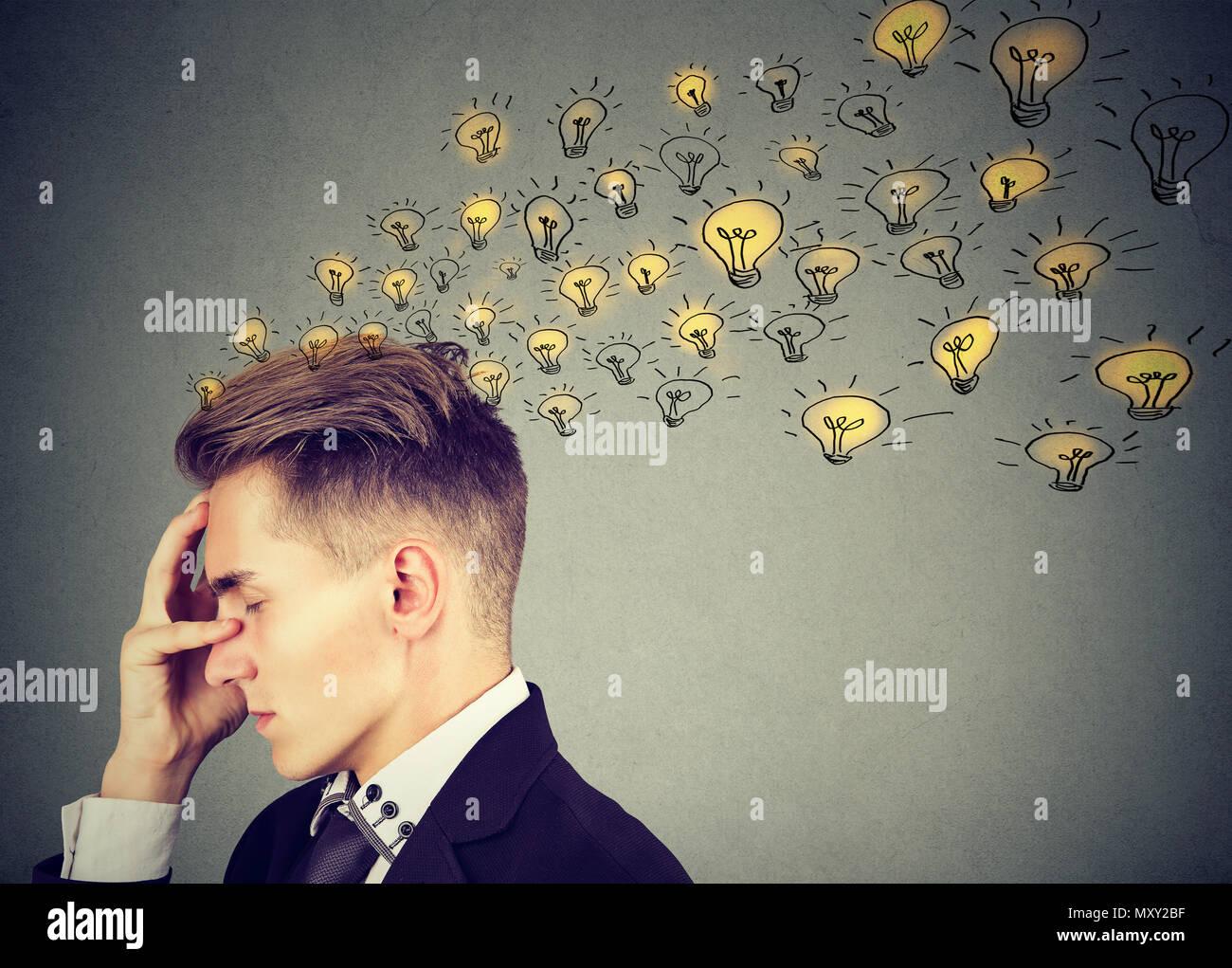 Contemplando hombre sujetando la mano sobre la frente y crear un montón de ideas brillantes sobre fondo gris Imagen De Stock