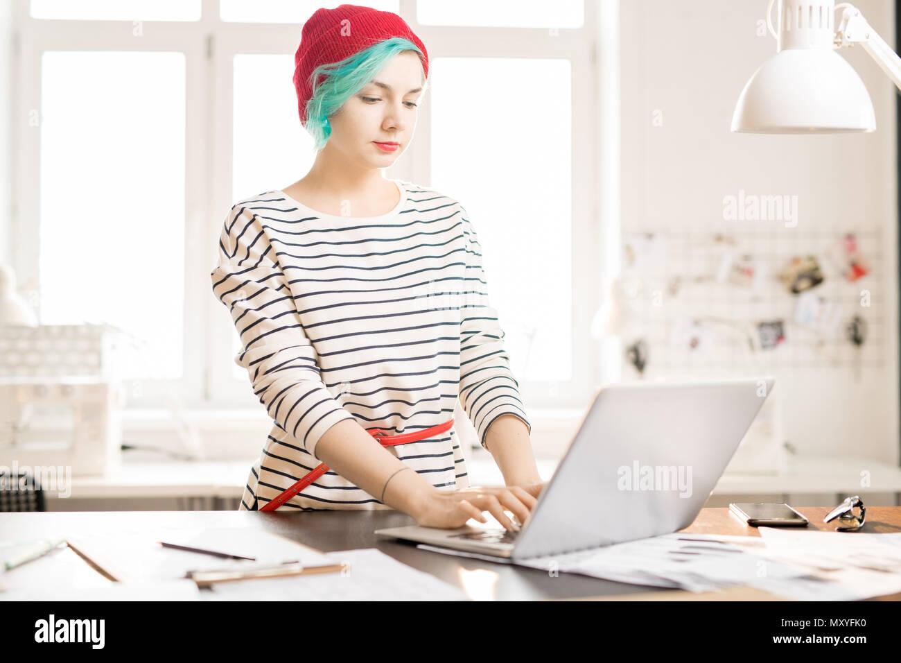 Cintura para arriba retrato de mujer joven contemporáneo con cabello verde utilización portátil mientras se trabaja en el proyecto de diseño de moda creativo en pequeñas atelier studio Imagen De Stock